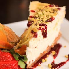 Le gâteau aux fromages, pluie de pistache & coulis de fruits
